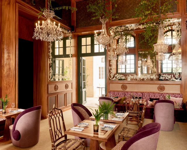 Dining area of Cafe Laperouse with chandeliers, wood details, and comfortable seating.