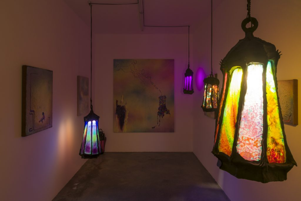 """The interior of Dani Tull's """"Slow Burners"""" exhibit with hanging lanterns lit up."""