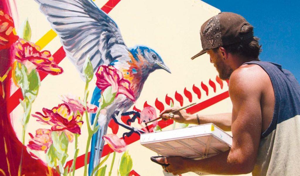 Artist Steven Teller painting a mural of a bluebird amongst flowers.