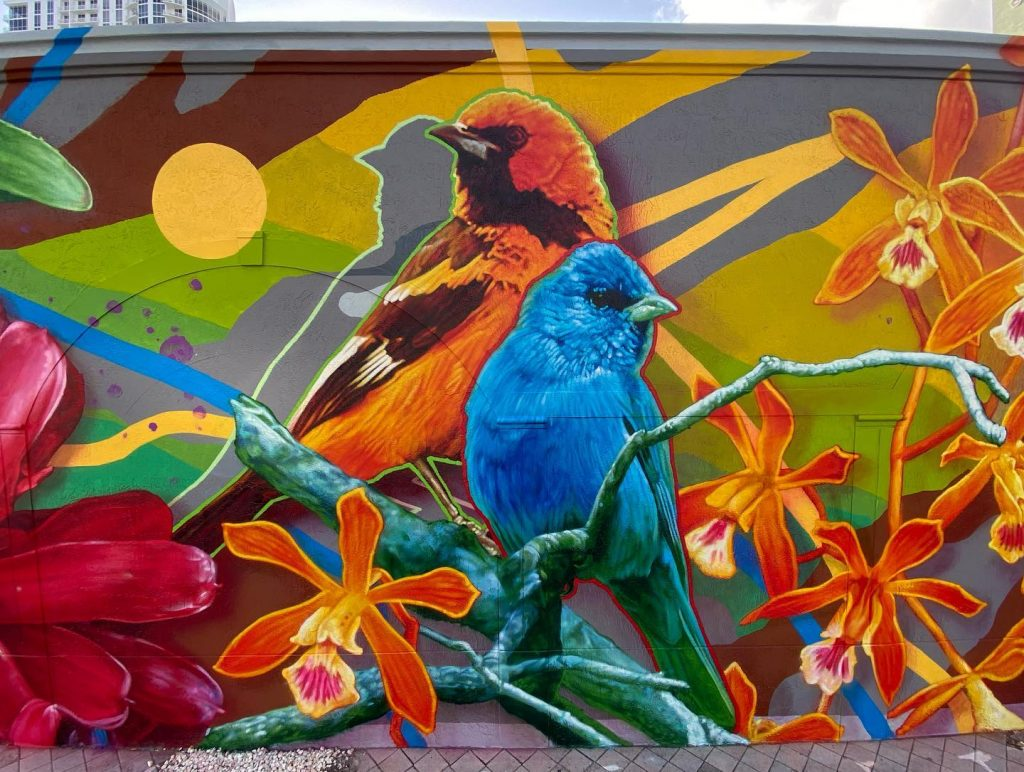 A colorful mural by Steven Teller of two birds perched on a branch surrounded by florals and abstract design.