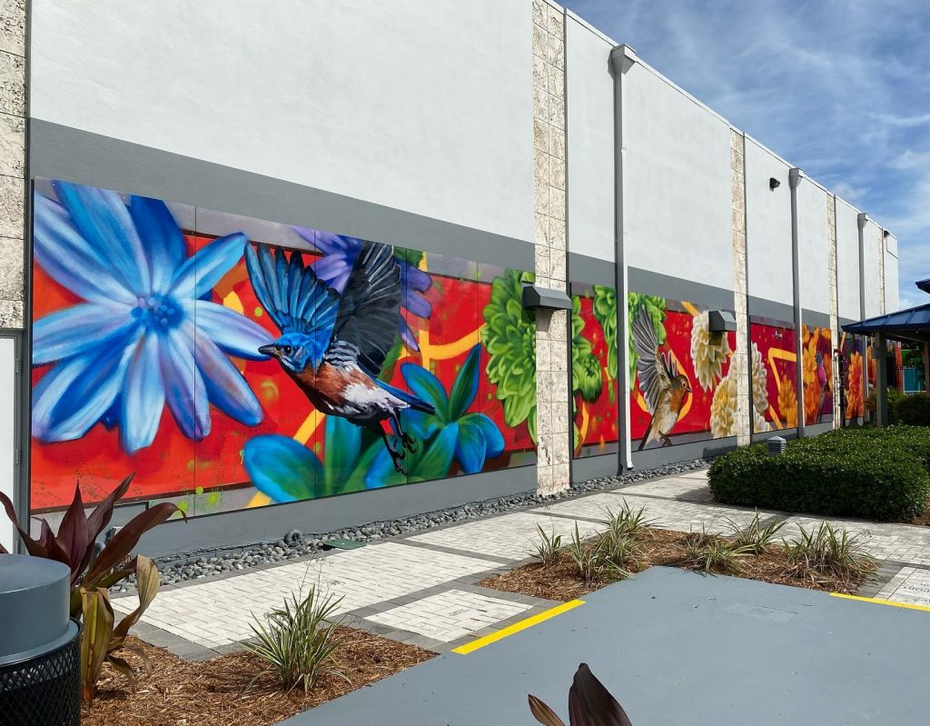 Part of Steven Teller's mural at the Pride Center with floral and bird imagery.