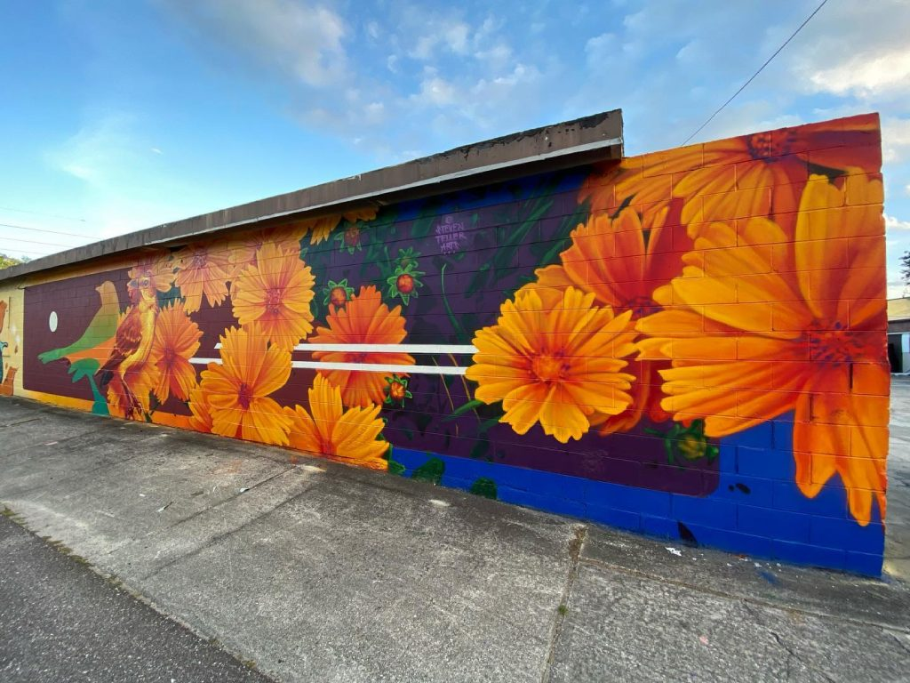 A vivid mural of orange flowers and a bird with its silhouette.