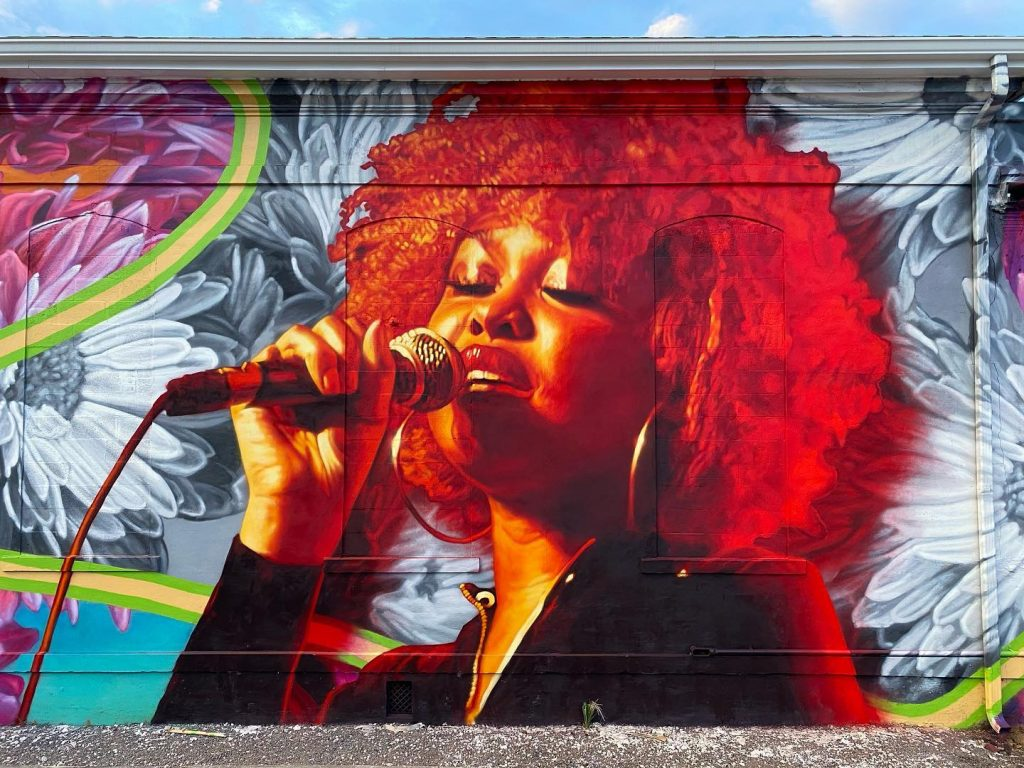 A mural of a portrait of an African American woman holding a microphone and singing.