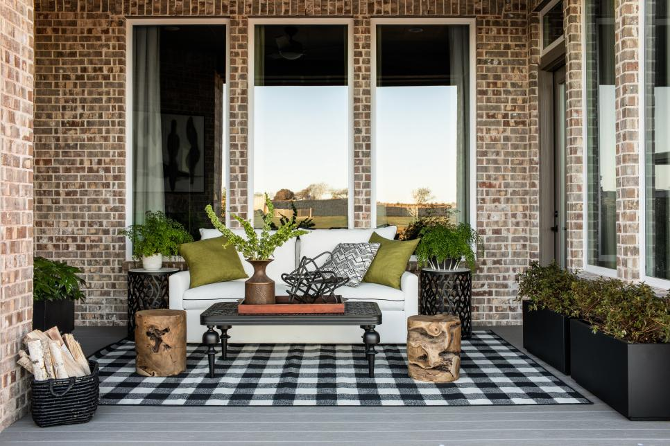 An outdoor living space with a buffalo check rug, outdoor sofa, green pillows, and basket of firewood.