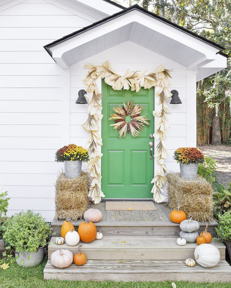 A green exterior door with a wreath and garland made out of corn and corn husks.
