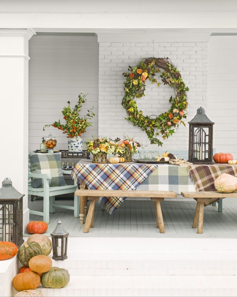 An outdoor space decorated for fall with an oversized wreath and plaid blankets on the table.