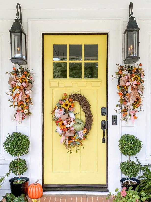 A yellow exterior door with festive wreath and decor that has pink details.