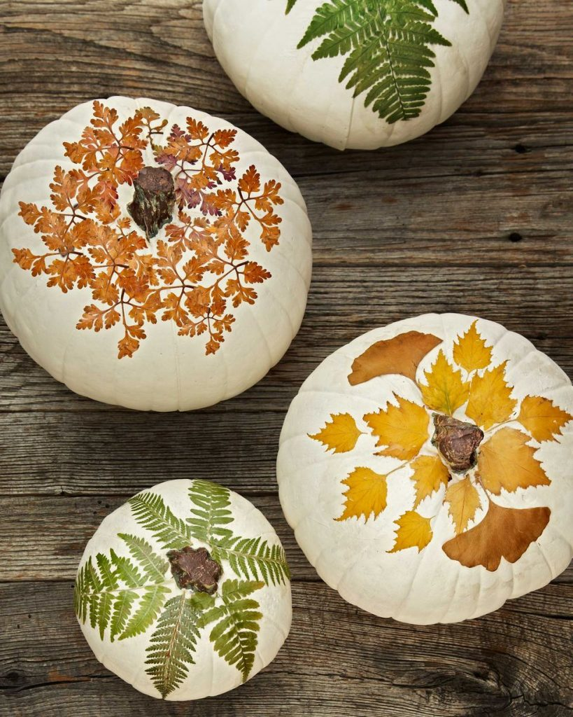 An overhead shot of pumpkins painted white and pressed autumn leaves decoupaged on.