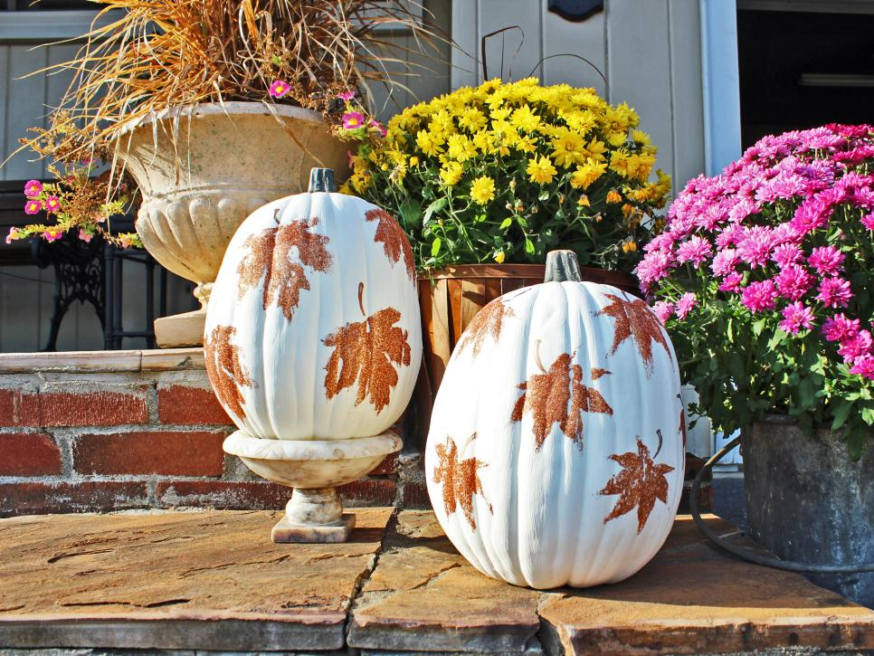 Two pumpkins painted white with glittery leaf design.