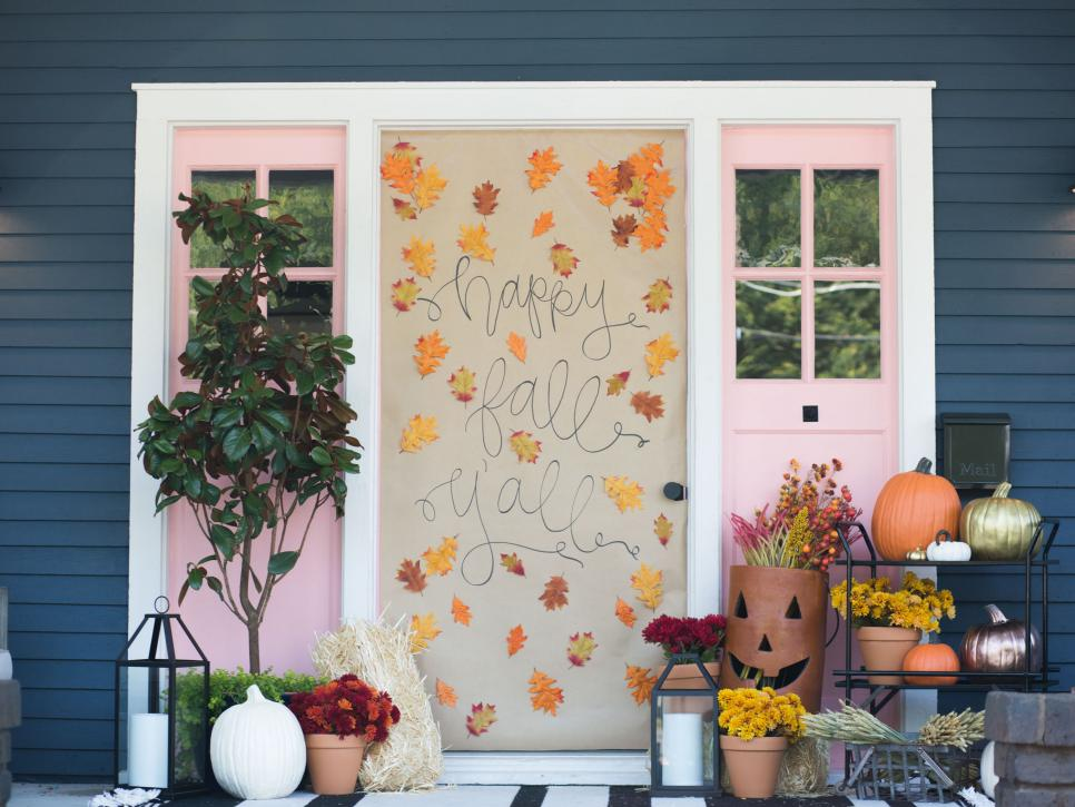 """An exterior door with brown paper over it with the message """"happy fall y'all"""" and leaves attached."""