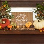 """Close up shot of a mantel decorated for wall with wooden sign that says """"gather"""" in the center."""