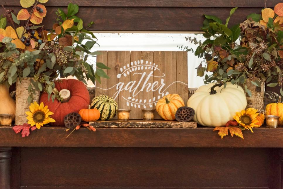 """A fireplace mantel decorated for fall with a wooden sign that says """"gather"""" in the middle."""