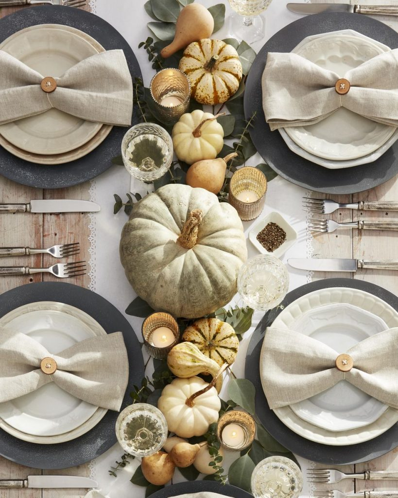 An overhead shot of a neutral tablescape with neutral pumpkins and candles lined up in the middle.