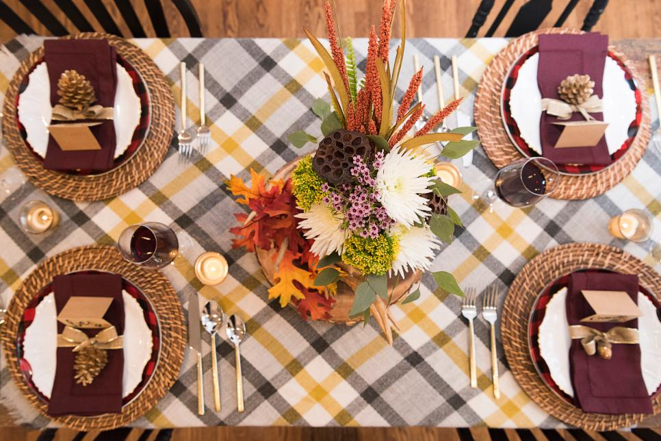 An overhead shot of a table scape with a plaid table runner and plates with name cards and gold pinecones.