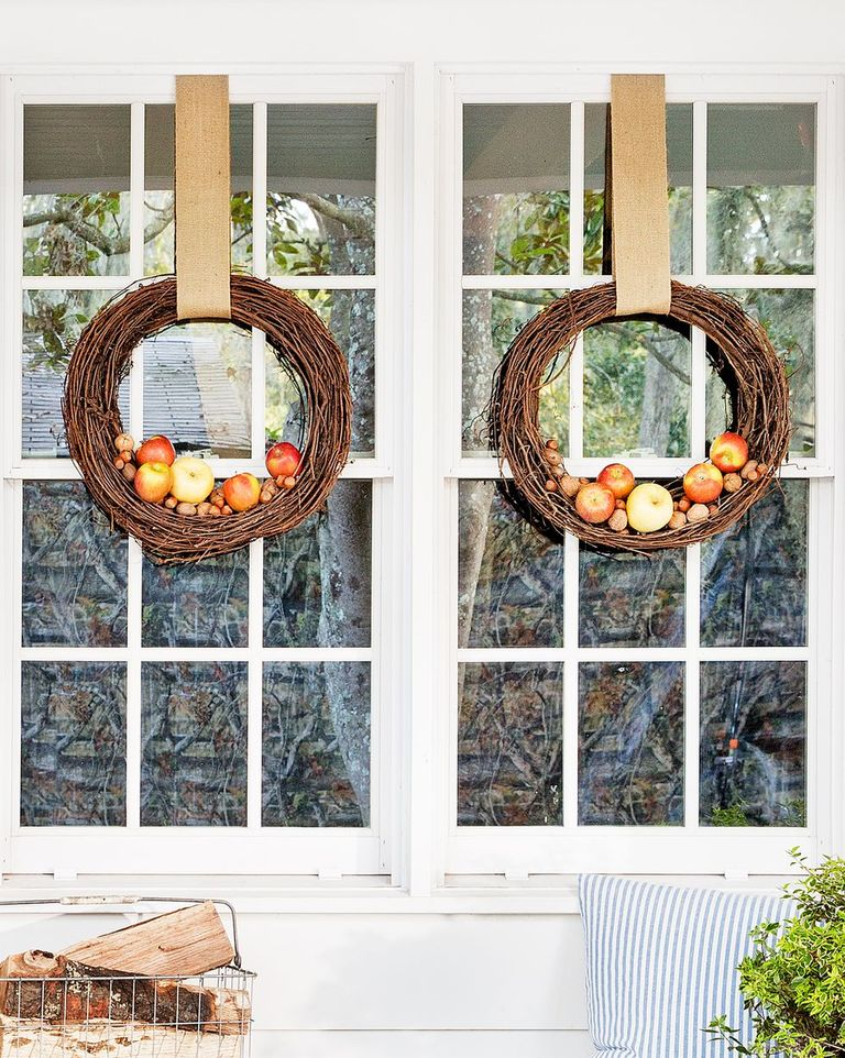 A window with two wreaths on it with apples attached.